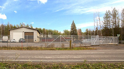 A warehouse property and the yard is protected and demarcated with chain link fencing and a sliding gate.